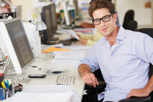 Man Working At Desk In Busy Creative Office — стоковое фото