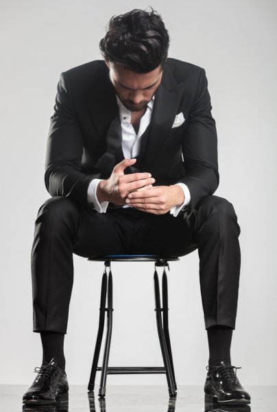 Man in tuxedo looking down while sitting on a stool, — стоковое фото