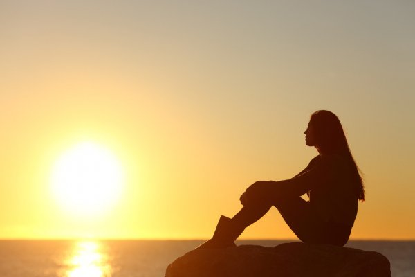 Woman silhouette watching sun in a sunset — стоковое фото