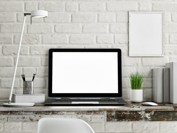 Laptop on wooden table, white brick wall — стоковое фото