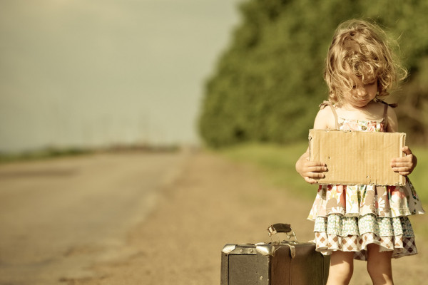 Lonely girl with suitcase standing about road — стоковое фото